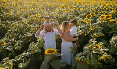 four people stand in a sunflower field smiling