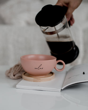 french press black coffee and a pink cup