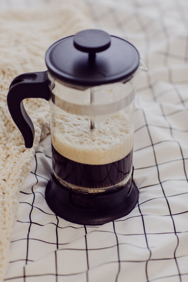french press with frothy black coffee on white blanket