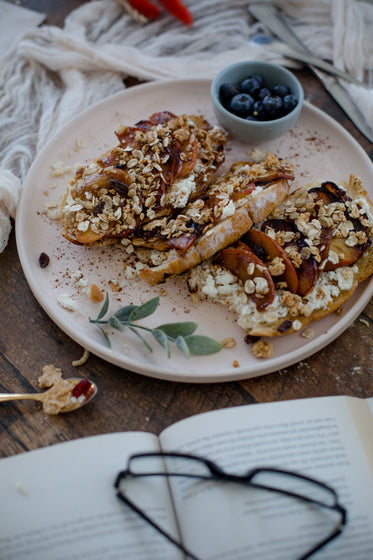 fresh bread covered in fruit with a book