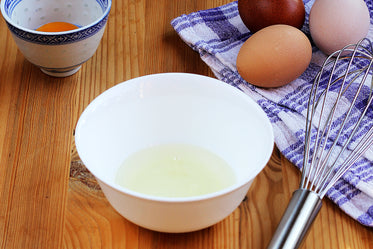 fresh eggs being separated into white bowl with whisk
