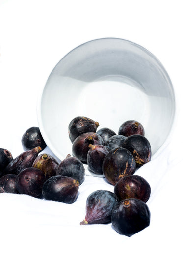 fresh fig fall out of a white bowl onto a blanket