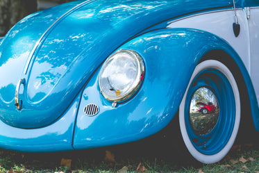 front of a bright blue classic car with round hood