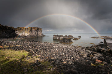full rainbow over rocks and water