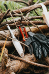 gardening tools leaning against a pile of wooden sticks