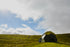 geodesic dome home stands tall in lush field of green grass