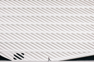 girl running past modern architecture