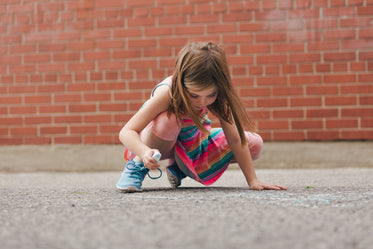 girl using sidewalk chalk in schoolyard