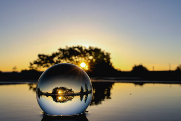 glass ball on water at sunset