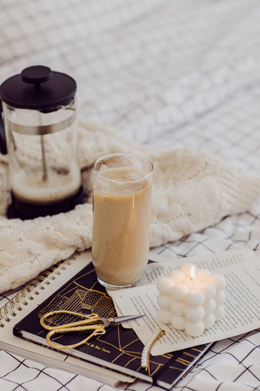 glass iced coffee a notebook and lit candle on a bed sheet