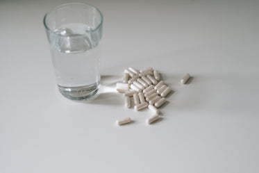 glass of water and pills on a white countertop