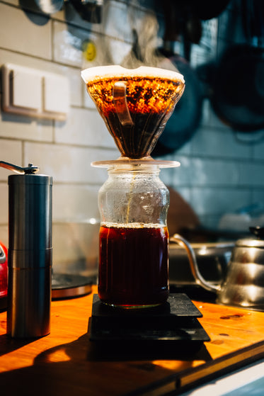 glass pour over coffee being brewed on wooden countertop