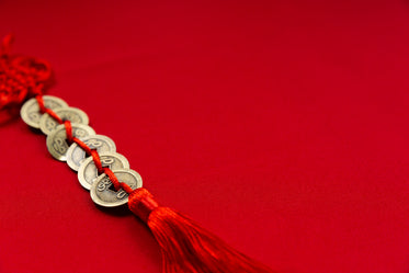 gold coins weaved onto red rope