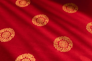 gold pattern on red brocade fabric