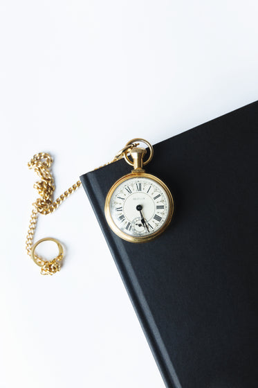 gold pocket watch on a black notebook