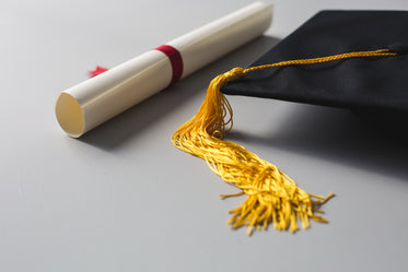 gold tassle graduation cap and diploma