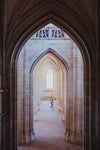 gothic archways in a corridor lead to a gothic window