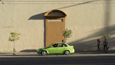 Picture of Green Car Passes Wall — Free Stock Photo