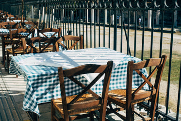 green gingham table cloth and wooden chairs