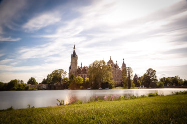 green grass by a lake and castle