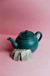 green teapot sits on a pink background with fresh tea bags