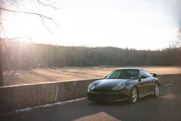 grey car is parked by a stone wall