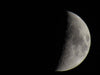 half of the moon against a black night sky