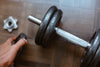 hand adding more weight to a dumbbell