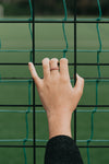hand grasping a black fence