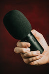 hand grips a black microphone against red background