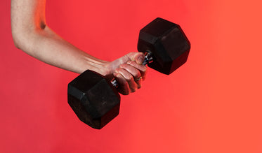 hand grips a dumbbell against a vibrant red background