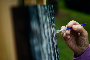 hand holding a fine paint brush to a painting