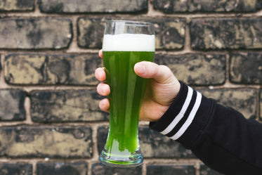 hand holding a green beer celebrating st. patricks day