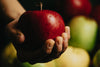hand holding a red apple with water droplets