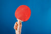 hand holding ping pong paddle on blue background