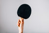hand holding ping pong paddle on grey background