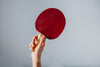 Hand Holding Red Ping Pong Paddle On Grey Background