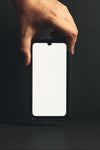 hand holds a cell phone over a black background
