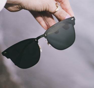 hand holds a pair of black sunglasses