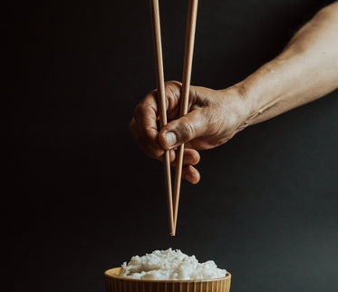 hand holds chopsticks over a bowl of rice