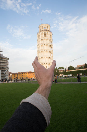 hand holds leaning tower