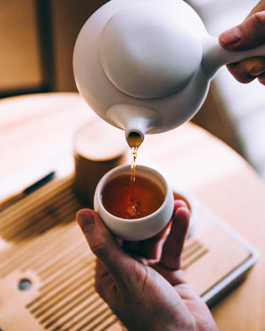 hand pouring hot tea