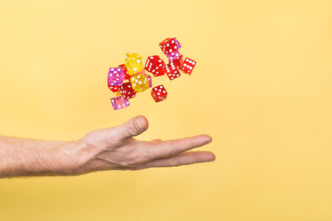 hand throwing dice on yellow
