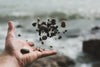 hand tossing pebbles