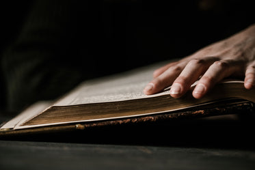 hand traces lines on large old bible