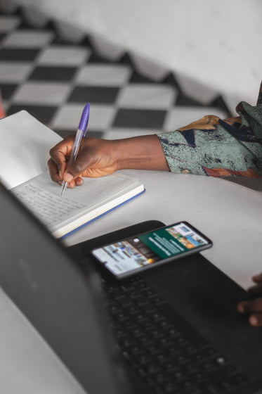 hand writes in a notebook by a laptop and cellphone