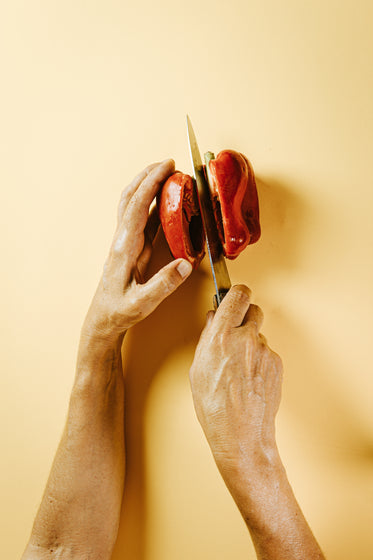 hands cut a red pepper with a sharp knife