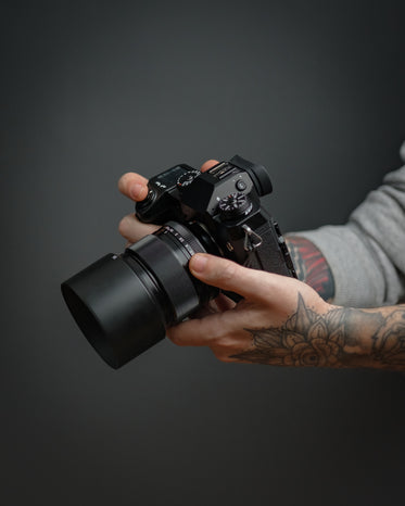 hands hold a black camera against a grey background