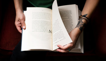 hands hold a novel and turn the page