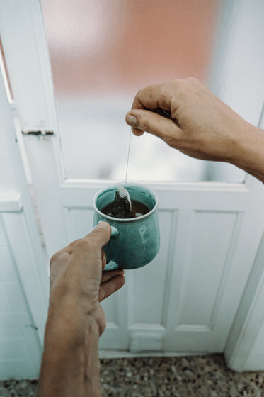 hands hold a tea bag and mug in front of a door